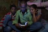 Indian family in light from glowing phone screen