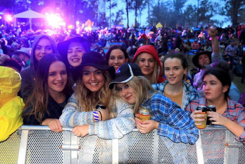 A group of girls gather near security barriers in front of a music stage.