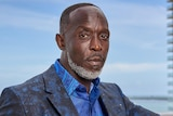 Michael K Williams looks at the camera while posing in a dark blue suit.