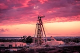 A mining headframe at a gold mine with the sun setting in the background.