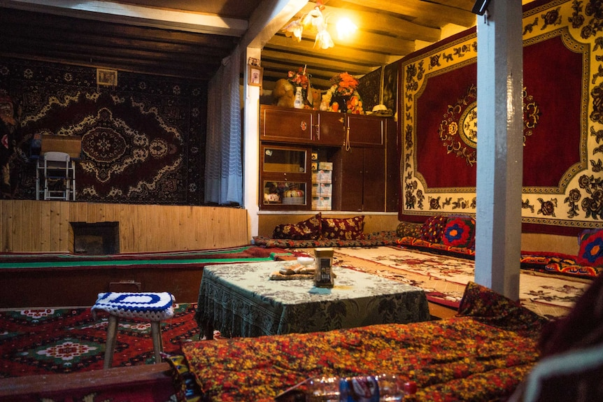 A richly decorated room with rugs on the walls