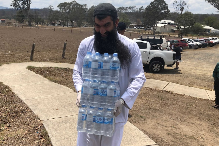 A man carries water for a barbecue