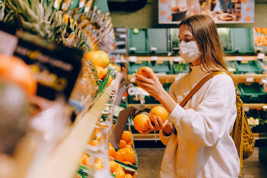 A woman wearing a face mask grocery shops.
