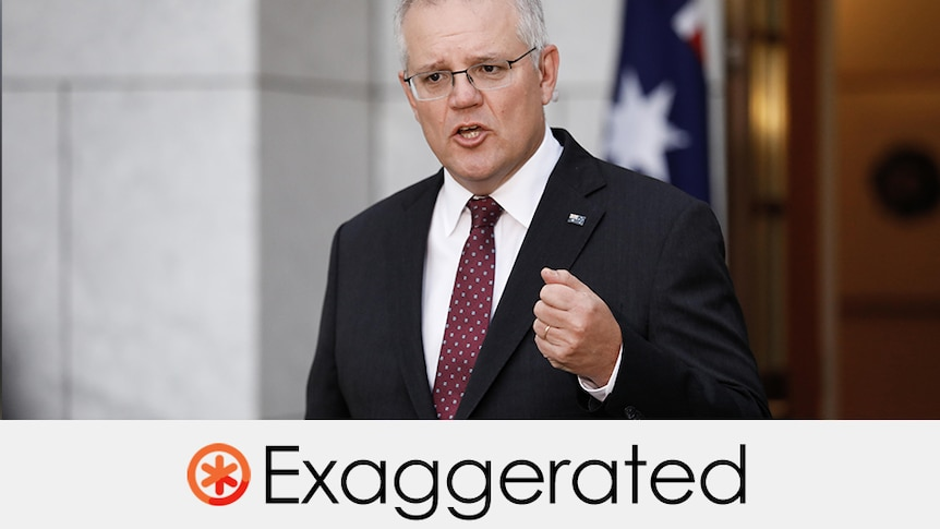 Prime Minister Scott Morrison wears a suit and gesticulates in front of Australian flag.
