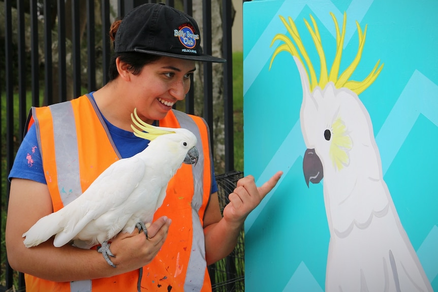 Tanya Rivera holding her pet cockatoo on her arm while showing it a painting of a white cockatoo.