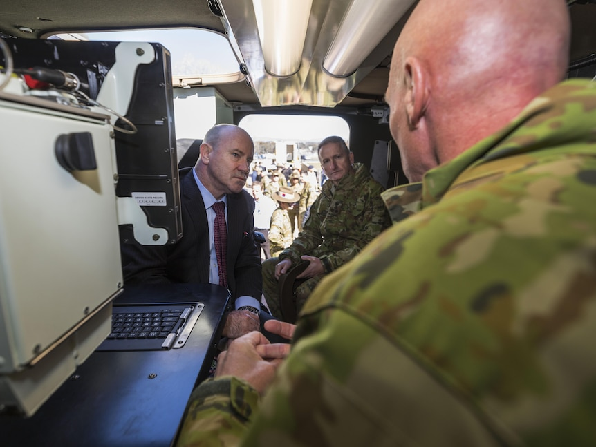 Three men sitting in a small space, one with his back to the camera in army uniform, another two looking at him while he speaks