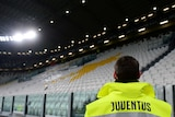 Juventus is written on the back of a steward's high-vis jacket as he looks at empty seats in a stadium.