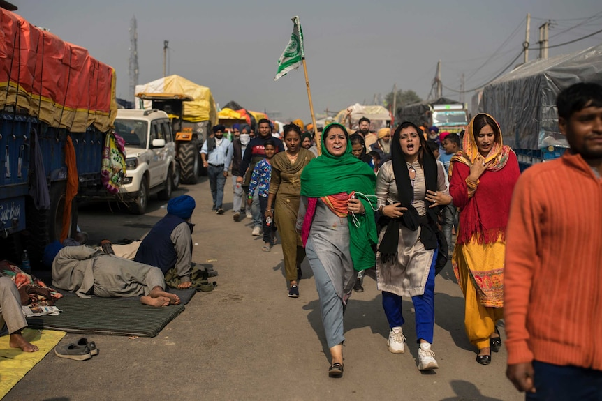 A group of women shout slogans as they arrive to join protesting farmers at the border between Delhi and Haryana state