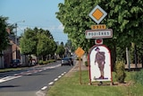 A road side sign for Pozieres with the picture of an Australian soldier on it.