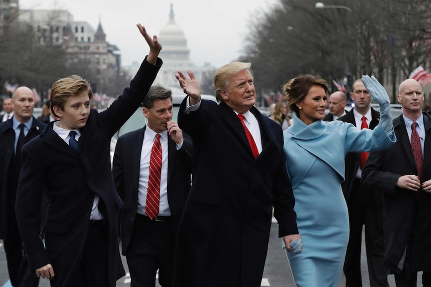 President Donald Trump waves as he walks with first lady Melania Trump and their son Barron during inauguration parade.