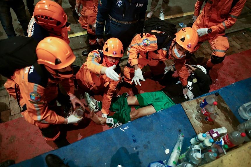 Several paramedics in orange uniforms treat an injured protester