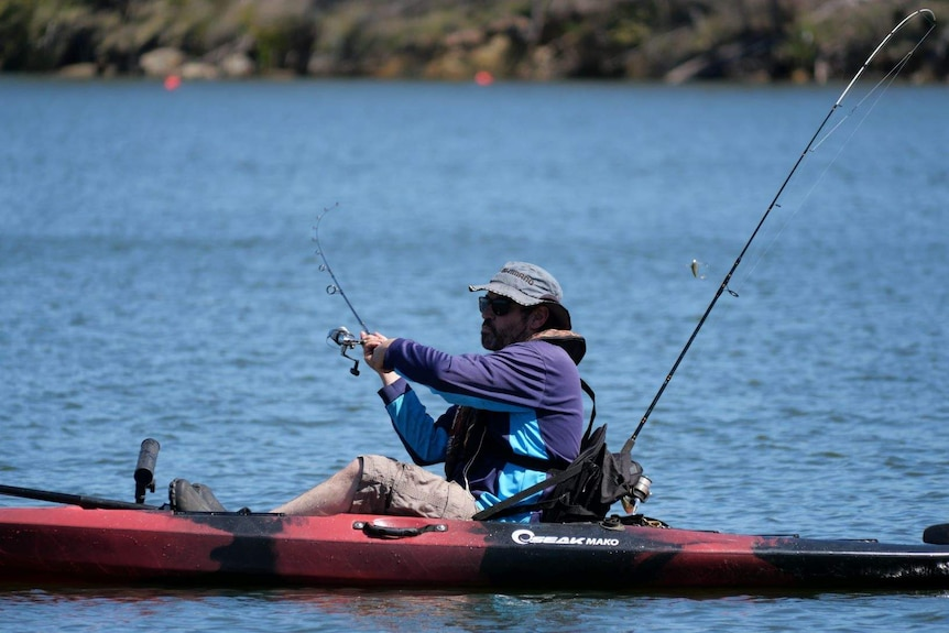 A paddler casts a line out to catch a fish.