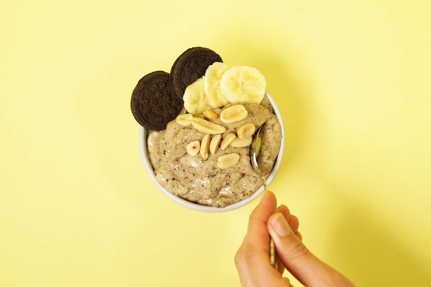 Banana nice cream in a bowl topped with chocolate cookies, peanuts and banana slices.