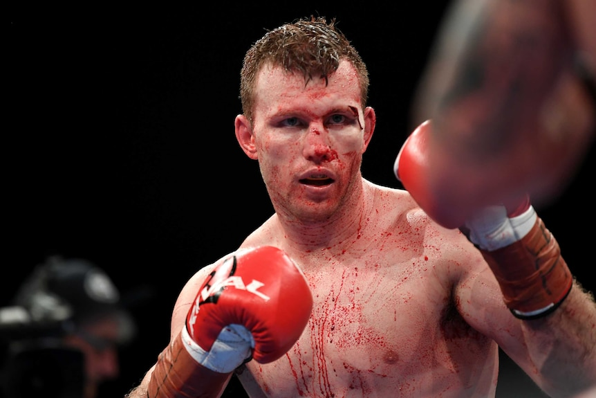 Jeff Horn holds a boxing stance with blood on his torso from a cut above his eye