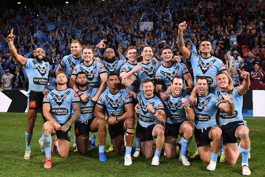 NSW Blues players pose for a celebratory photo on the field after winning the 2021 State of Origin series.
