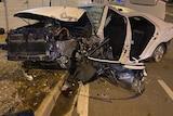 A badly damaged white sedan