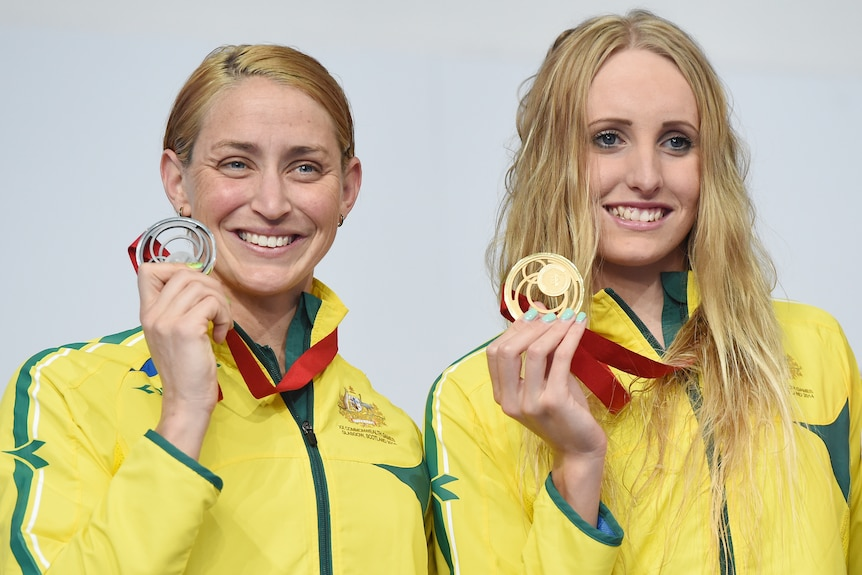 Two Australian female swimmers show off their 2014 Commonwealth Games medals.