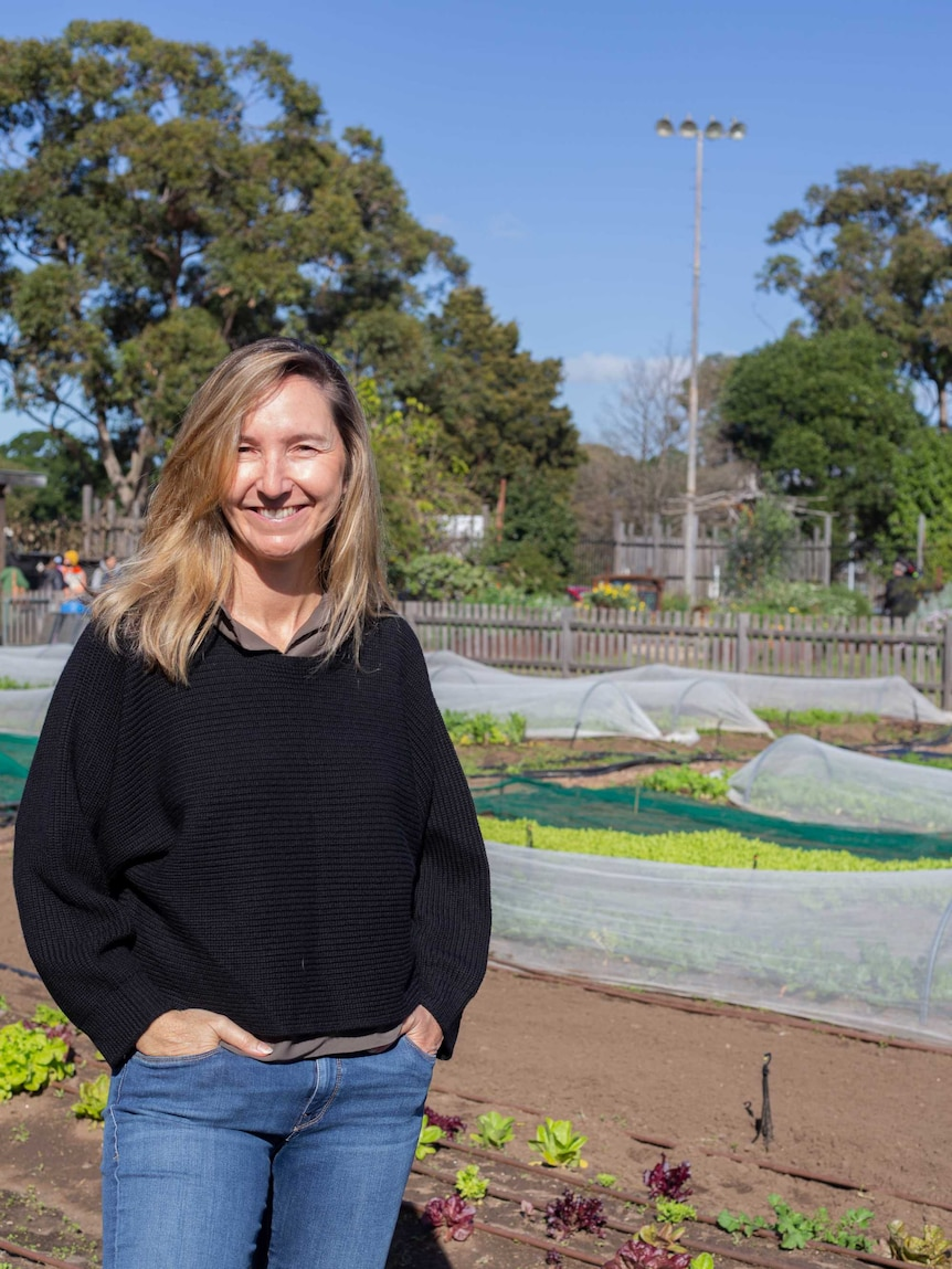 A smiling woman standing in front of garden beds.