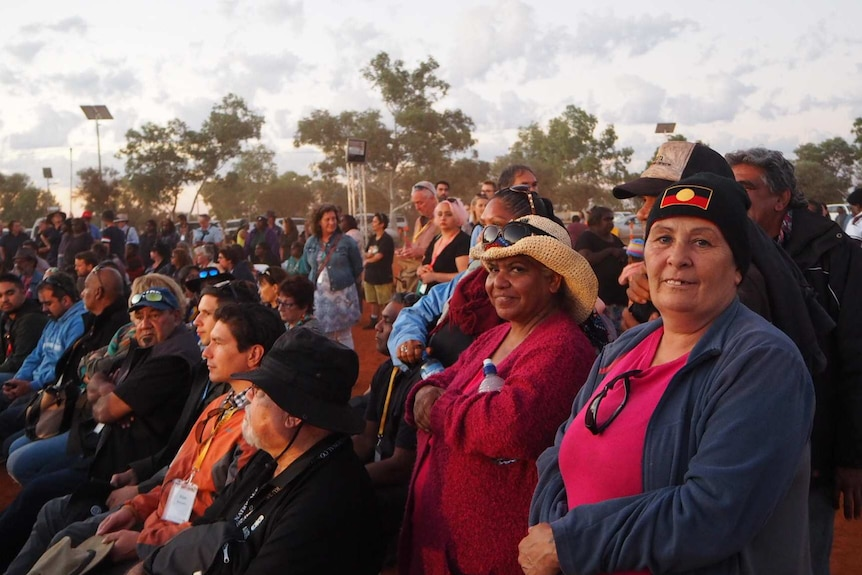 A crowd of people watching talks at the constitutional recognition summit in Uluru, two women look at the camera smiling.