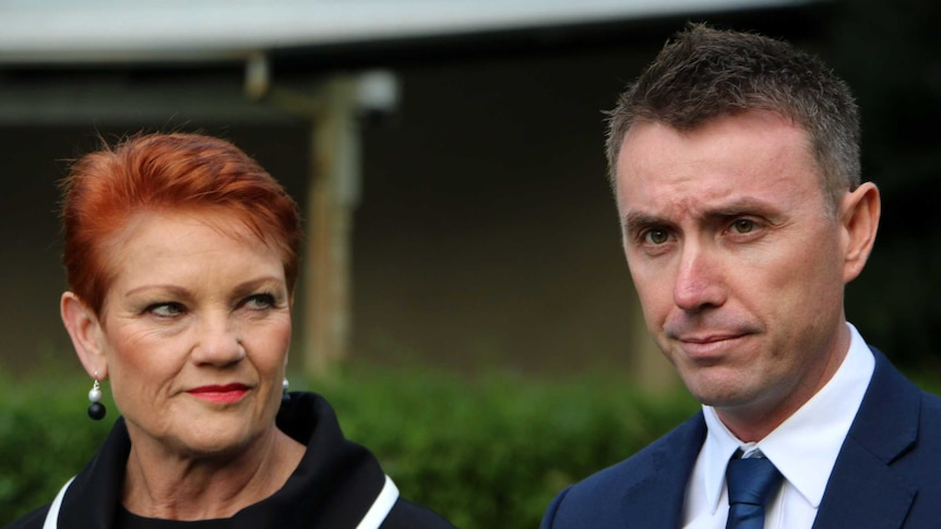 Pauline Hanson looks at a grim looking James Ashby at a press conference. The background is out of focus.