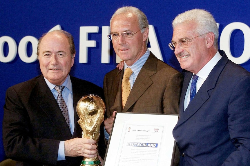 FIFA president Sepp Blatter (L) with the World Cup, Franz Beckenbauer (C) and Fedor Radmann (R).