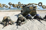 Marines from the US and South Korea take positions on a beach after landing in joint military exercises.