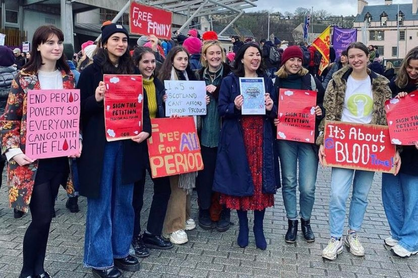 On an overcast day, you view a group of women holding placards advocating for universal period products.