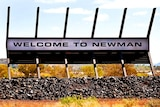A 'Welcome to Newman' sign on mining equipment installed on the edge of town.