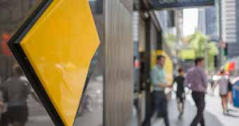 A Commonwealth Bank sign in the foreground with people blurred walking by in the background
