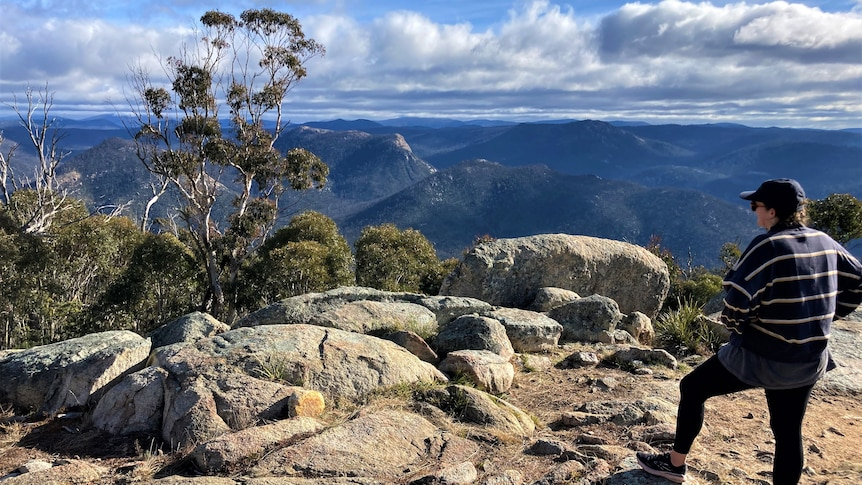 A bushwalker stands with their foot on a rock looking at a vast view, clouds in the distance.