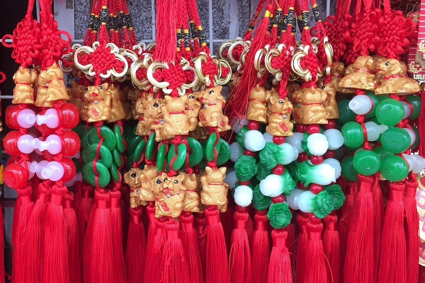Decorations show small dogs with green and red beads and red tassels.