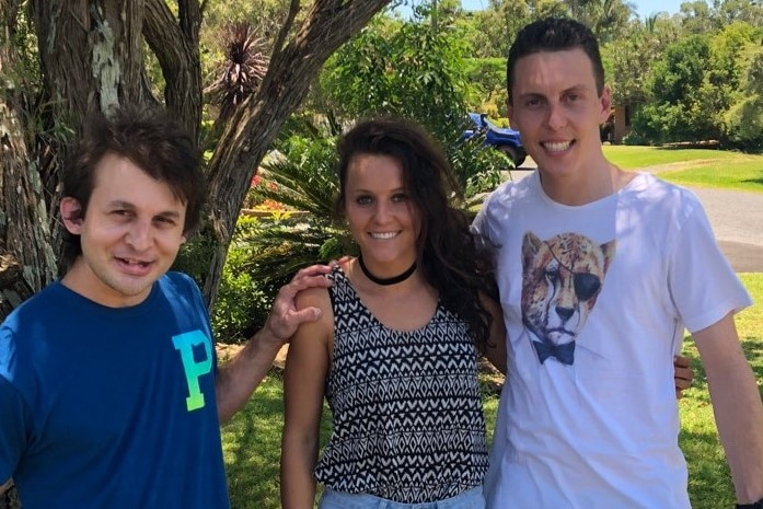 Hayley Raso stands in between her brothers in front of a tree.