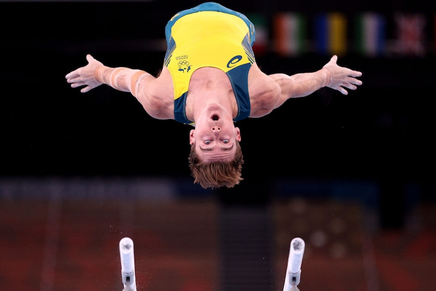 Australian gynmast Tyson Bull is photographed upside down in the air from the ground. He is looking at parallel bars below