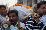 The brothers of rail crash victim Narendra Sinhu carry his body to the Ganges for cremation.