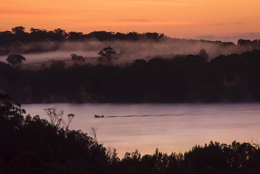 A boat on a lake at dawn with fog rising from the land