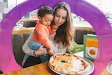 Mum with her toddler son in front of a pizza