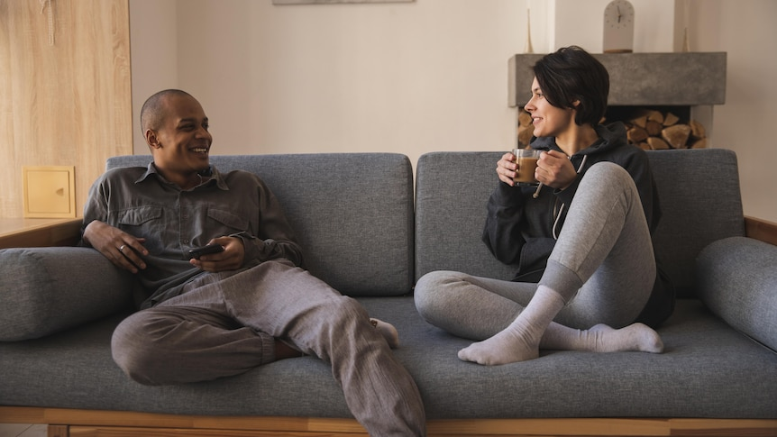 Man and woman sitting on couch chatting in a story about how men benefit from talking about their feelings
