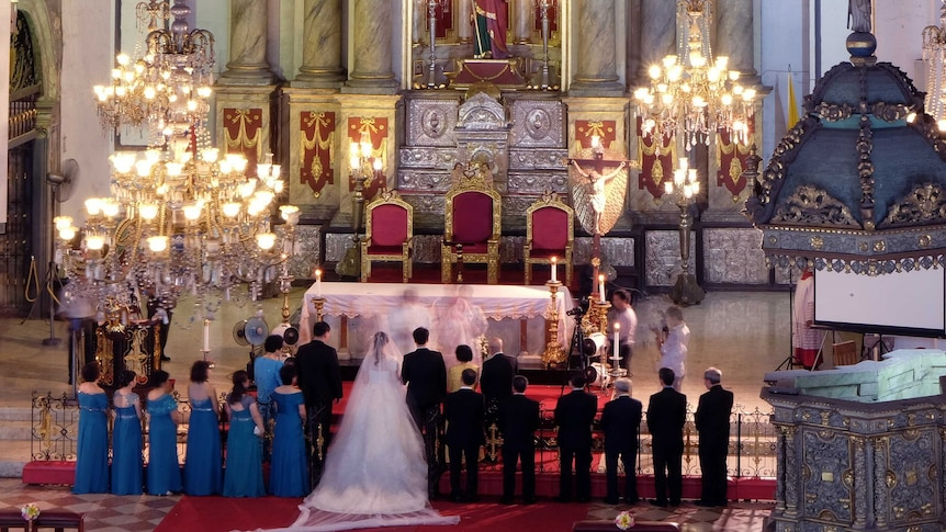 A man and a woman get married in a grand Christian church surrounded by bridesmaids and groomsmen.