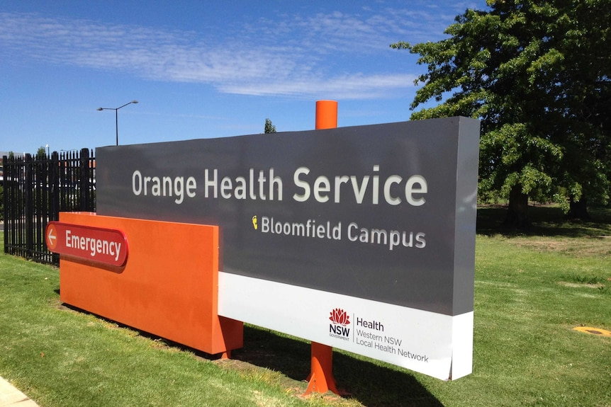 A sign at the entrance to a facility says 'Orange health service'.