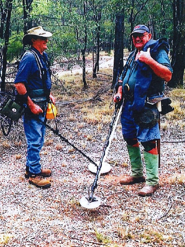 Paul and John stand in the bush with their metal detectors.