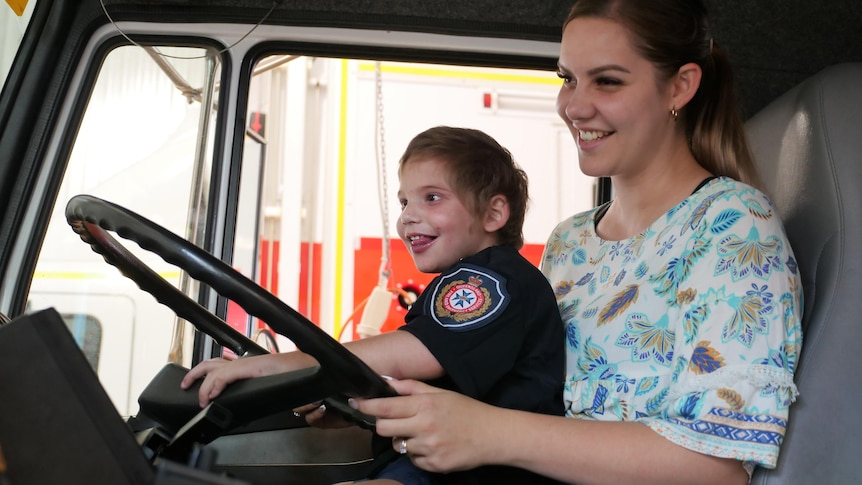 a young boy in a firefighting uniform sits on his mother's lap touching the steering wheel