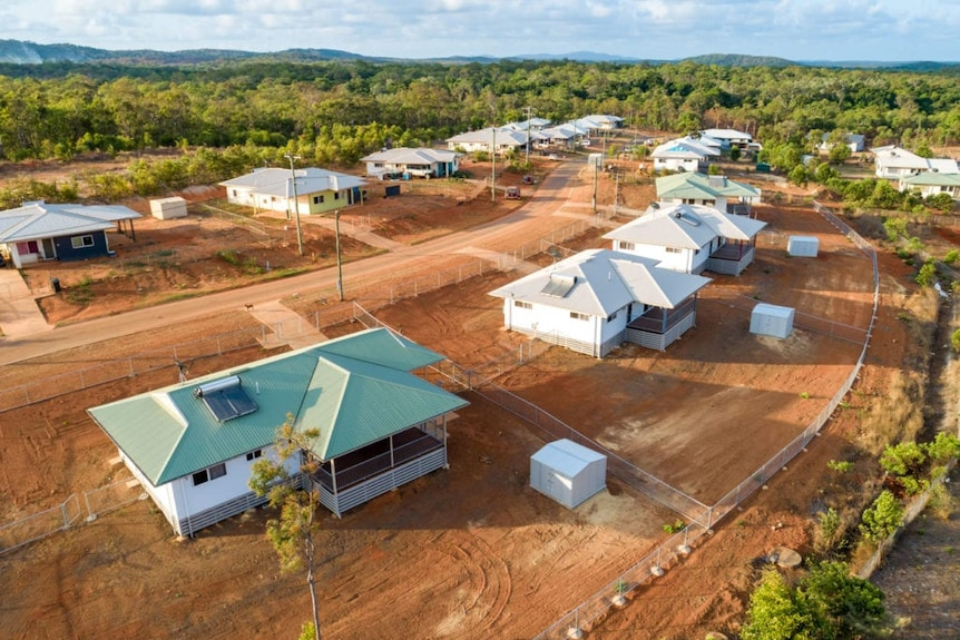 An aerial view of a new housing estate on red dirt surrounded by trees.