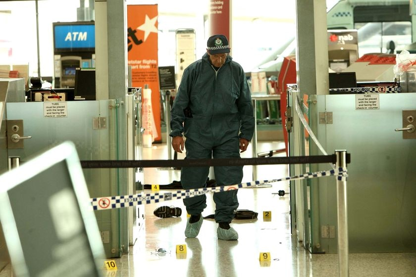 A police officer walks through the scene at Sydney airport where a man was bludgeoned to death
