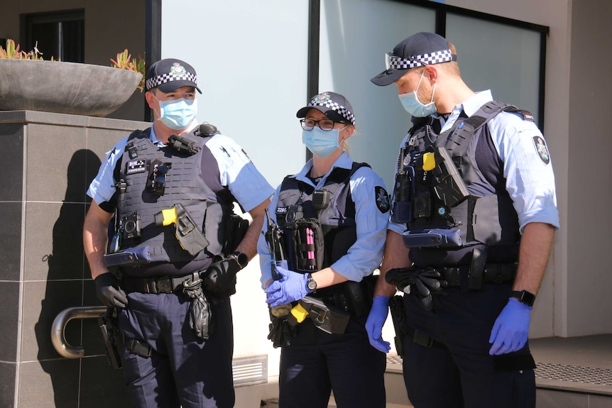Three police officers wearing masks on duty in Canberra.
