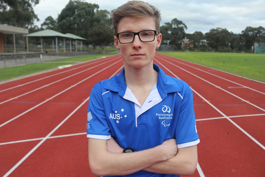 Jaryd Clifford stands in in the middle of a running track wearing a Paralympics Australia shirt.