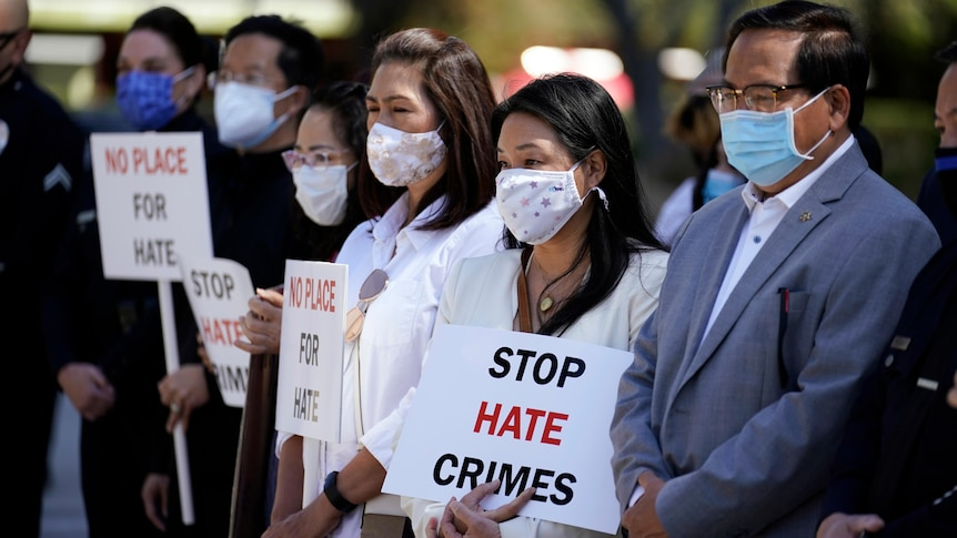 A group of face-masked Asians hold Stop Hate Crimes signs in a line on a sunny day.