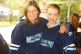 """Two teenaged girls stand arm in arm with """"Marryatville Seniors"""" written on their school uniforms."""