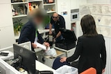 ASIO officer puts files into bag while cameraman films him.