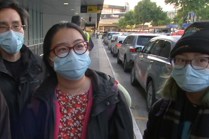 Four people - two men, two women - wearing medical masks stand on the footpath outside the Melbourne airport.