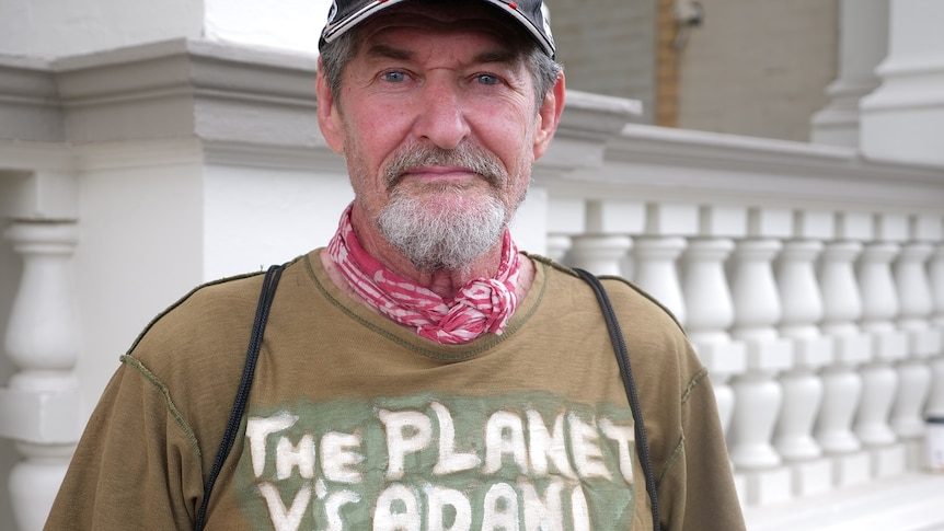 "Chris Hooper looking at the camera, straight face, facial hair, blue eyes, wearing a cap, t-shirt says ""the planet vs adani""."